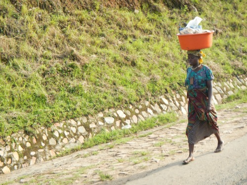 Woman in Uganda walking on side of road while balancing a head basket.
