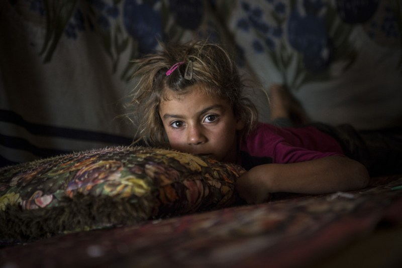 Suhad * six, lies on the floor of her home in a tented refugee settlement in Lebanon, near the Syrian border. *Names have been changed to protect children's identities. Jonathan Hyams/Save the Children