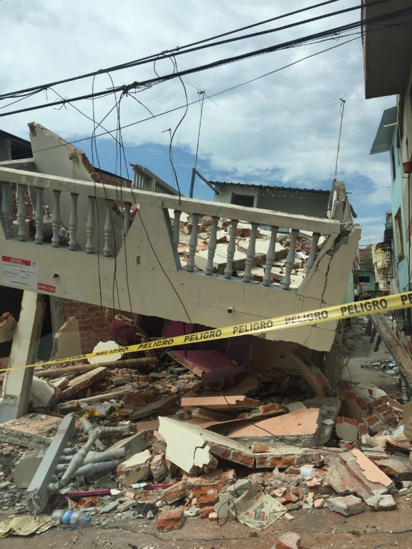 "Yellow tape marked ""Peligro"" warns people of danger after the roof and balcony collapse of a building in Manta, Ecuador after the earthquakes in April 2016."