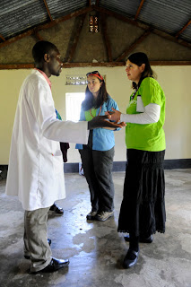 Jennifer Burden of World Moms Blog and Cindy Levin of RESULTS talk to a lab technician in Fort Portal, Uganda, while there with a delegation from the Shot@Life campaign.  Photo credit to Stephanie Geddes.