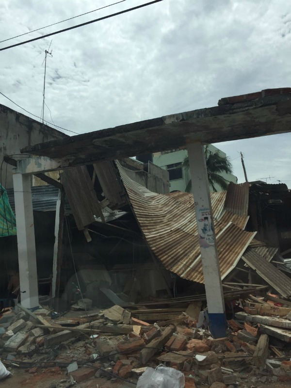 A tin collapsed and bent tin roof and tilted building supports lean atop brick rubble in the aftermath of the earthquakes in Manta, Ecuador in April 2016.